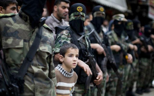 Un jeune garçon se tient au milieu de Palestiniens du Jihad islamique, dans la bande de Gaza (Crédit : Mahmud Hams/AFP)