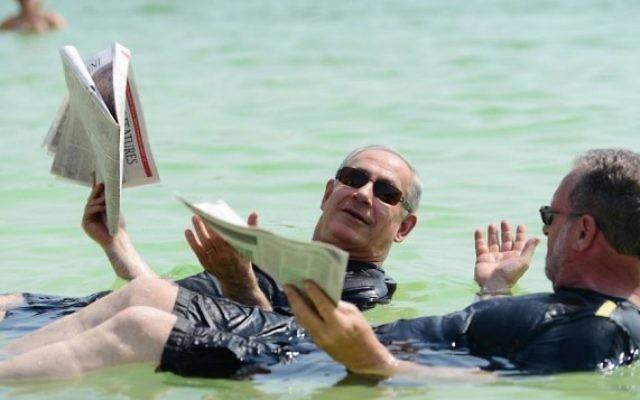 """Le Premier ministre Bejamin Netanyahu flotte dans la Mer Morte avec le producteur Peter Greenberg, lors de leur """"Visite Royale"""" d'Israël. (Crédit : Kobi Gideon/Bureau de presse du gouvernement)"""