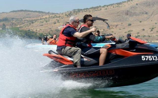 """Le Premier ministre Bejamin Netanyahu à bord d'un jet-ski sur la mer de Galilée lors de sa """"Visite Royale"""" avec le producteur Peter Greenberg (Crédit : Avi Ohayon/Bureau de presse du gouvernement)"""