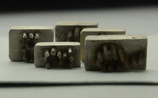 Cinq originaux rares de plaques métalliques à aiguilles trouvés à Auschwitz (Crédit : AFP)