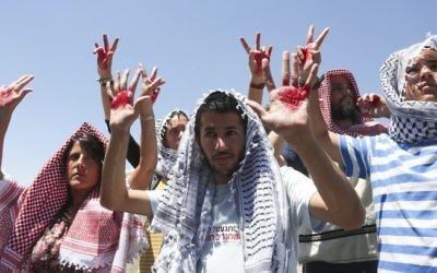Des Israéliens recouverts d'un keffieh pour protester contre la libération de prisonniers (Crédit : Flash 90)