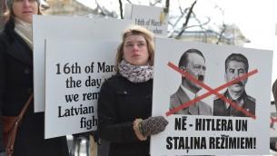 Des Lettoniens manifestant contre la marche annuelle des anciens combattants des Waffen SS à Riga, le 16 mars 2014 (Crédit : AFP/Ilmars Znotins)