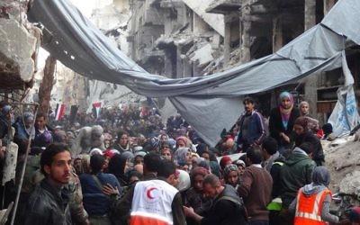 Des Palestiniens évacués du camp de réfugiés de Yarmouk à Damas, Syrie 2 février 2014 (Crédit : UNWRA/AFP)