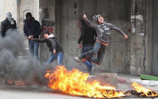 Des Palestiniens jettent des pierres sur les forces de sécurité israéliennes à Hébron le 17 mars 2014 (Crédit : AFP/Hazem Bader)