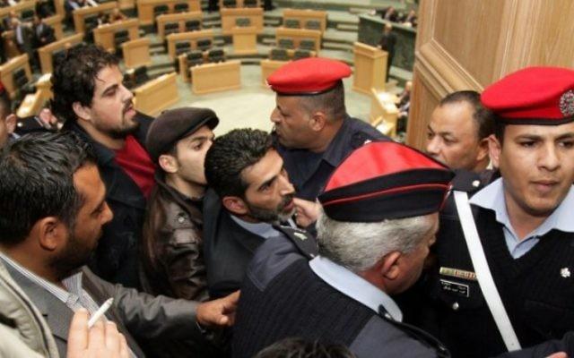 Des forces de sécurité escortent le militant qui a tenté de faire entrer le drapeau au parlement jordanien (Crédit : AFP)