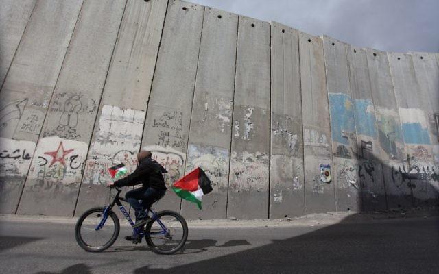 Une Palestinienne roule le long du mur de séparation près du quartier de al-Aizaria à Jérusalem, le 1er mars 2013 (Crédit : Issam Rimawi/Flash90)