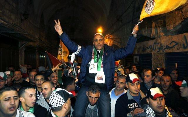 Des Palestiniens portent un prisonnier libéré le 3 janvier 2014 dans la  Vieille Ville de Jérusalem (Crédit : Sliman Khader/Flash90)