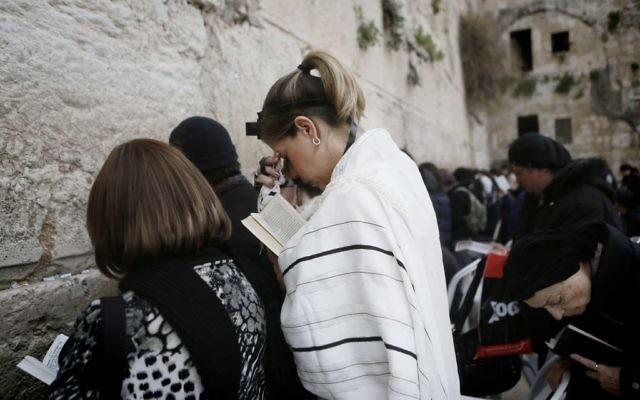 Une femme de l'organisation Neshot Hakotel porte les téfillines et le talith, normalement réservés aux hommes juifs orthodoxes, au Mur occidental, 3 mars 2014 (Crédit : Miriam Alster/FLASH90)