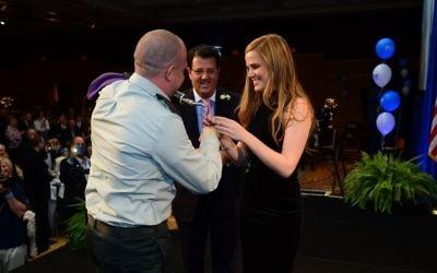 Le capitaine Ziv Shilon enfile une bague de fiançailles au doigt de sa fiancée, Adi Sitbon, lors d'un évènement des FIDF à Hollywood en Floride. (Crédit : Carlos Chattah/JTA)