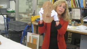 Le docteur Debby Hershman, la conservatrice du département de la culture préhistorique du musée d'Israël, tient un des masques dans les laboratoires du musée (Crédit : Ilan Ben Zion/Times of Israel)