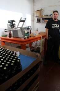 Tomer Ronen, l'un des brasseurs de la Brasserie du Néguev, utilise une machine pour étiqueter les milliers de bouteilles produites tous les mois (Crédit : Rebecca McKinsey/Times of Israel)