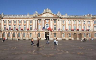 La façade de la mairie de Toulouse et au premier plan la croix occitane ornant le sol du Capitole (Crédit : Felipeh/CC.BY.SA/Wikimedia commons)