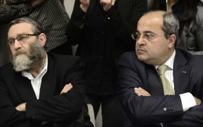 Le député arabe israélien Ahmed Tibi (à droite) assis aux côtés de Moshe Gafni à un meeting de l'opposition à la Knesset (Crédit : Tomer Neuberg/Flash90)
