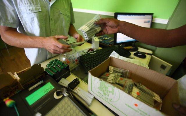 Un patient achète du cannabis médical à la pharmacie à Tel Aviv (Crédit : Abir Sultan/Flash 90)