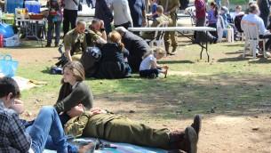 Après une marche nocturne de 50 kilomètres et la cérémonie, les soldats se reposent dans l'herbe avec leurs familles (Crédit : Rebecca McKinsey/Times of Israel)