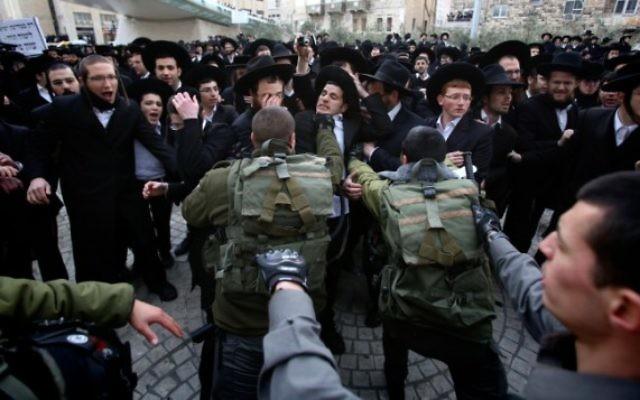 Des manifestants ultra-orthodoxes affrontent la police, le 6 février 2014 (Crédit : Yonatan Sindel/Flash90)