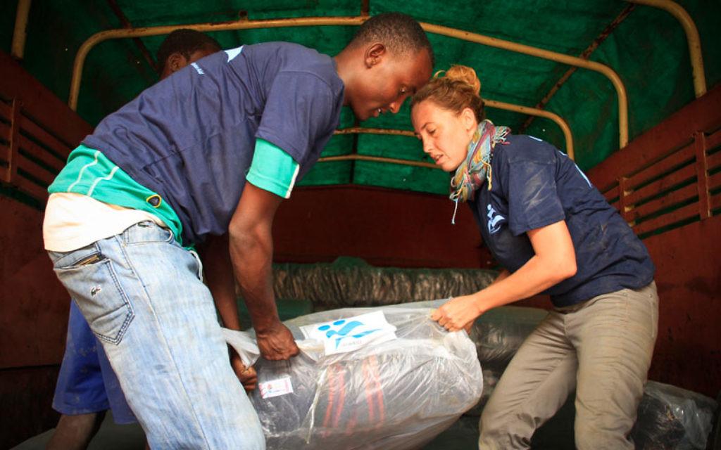 Une volontaire aide à décharger les dons de l'organisation IsraAID au camp de réfugiés de Kakuma au Kenya (Crédit : Autorisation d'IsraAID)