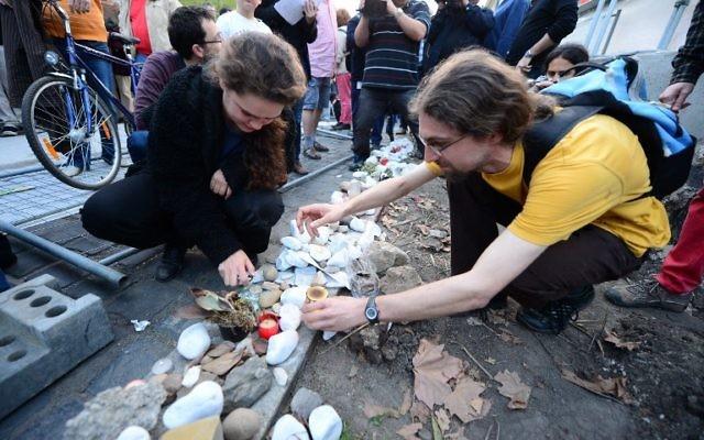 Des manifestants allument des bougies à la mémoire des victimes de l'Holocauste, à côté de l'endroit où un mémorial controversé devrait se construire à Budapest (Crédit : Attila Kisbenedek/AFP)