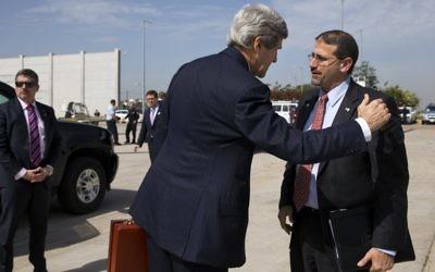 Le secrétaire d'État américain John Kerry salue l'ambassadeur américain en Israël, Daniel Shapiro, avant d'embarquer son avion à l'aéroport international Ben Gurion, le 1er avril (Crédit : Jacquelyn Martin/POOL/AFP)