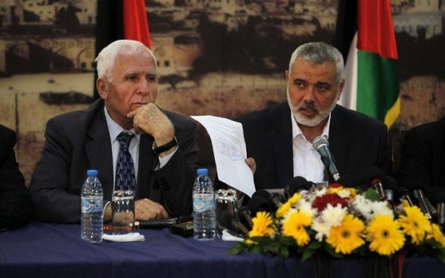 Le Premier ministre du Hamas à Gaza, Ismaël Haniyeh, présente l'accord de réconciliation lors d'une conférence de presse conjointe avec le chef de la délégation du Fatah, Azzam al-Ahmed, le 23 avril 2014 à Gaza (Crédit : AFP PHOTO / SAID KHATIB)