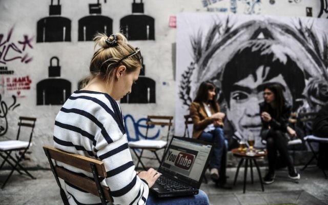 Une jeune femme utilise un ordinateur montrant le logo de YouTube, après que la Turquie a bloqué l'accès au site, le 27 mars 2014 (Crédit : Ozan Kose/AFP Photo)