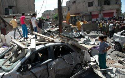 Le personnel d'urgence et les civils inspectent les lieux suite à l'attentat à la voiture piégée dans le quartier d'Abbasiyah dans la ville syrienne de Homs, le 29 avril 2014 (Crédit : AFP Photo)