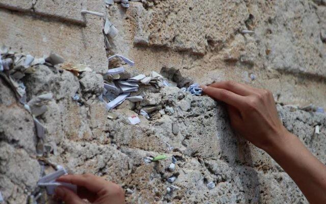 Une jeune femme insérant une prière dans le mur Occidental dans la Vieille Ville de Jérusalem (Crédit : Nechama Perton)