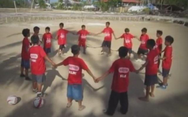 Des enfants jouant au football sur l'île de Bantanyan avec un éducateur de l'ONG israélienne Mifalot (Crédit : capture d'écran YouTube)