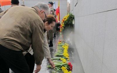 Des gens posent des fleurs à Umschlagplatz dans le ghetto de Varsovie, un monument à la mémoire des victimes de l'Holocauste (Crédit : Ruth Ellen Gruber/JTA)