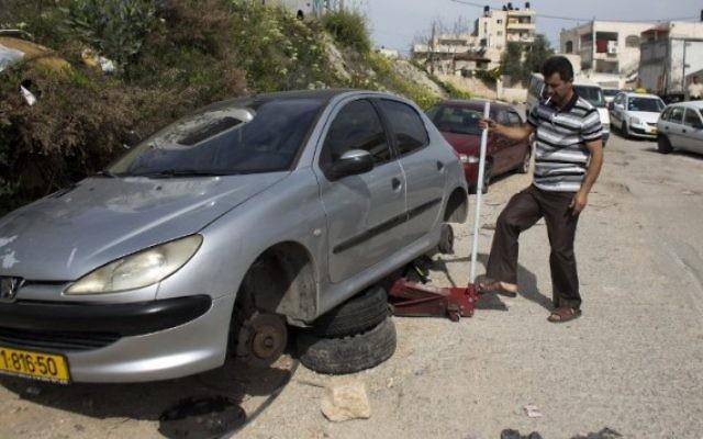 """A titre d'illustration: un Palestinien change les pneus de sa voiture après une attaque de type """"prix à payer"""" en mars 2014 (Crédit : Ahmad Gharabli/AFP)"""