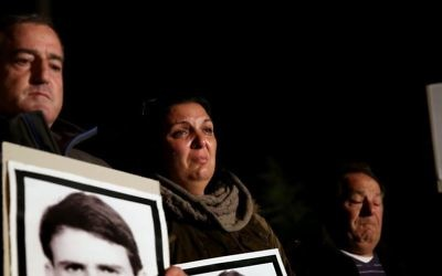 Des Israéliens, dont des membres de familles des victimes du terrorisme palestinien, portent des affiches et des photos de victimes, lors d'une manifestation contre la libération de prisonniers, devant la résidence du Premier ministre (Crédit : (photo credit: Hadas Parushl/Flash90)