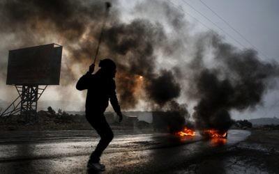 Image illustrant un Palestinien jetant des pierres vers les autorités israéliennes (Crédit : Issam Rimawi/Flash90)