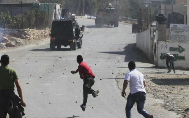 Palestiniens jetant des pierres sur un véhicule de l'armée israélienne. Illustration. (Crédit : Issam Rinawi/Flash90)