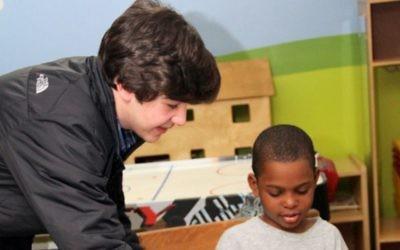 Nicholas Lowinger aidant un enfant à récupérer des nouvelles chaussures (Crédit : JTA)