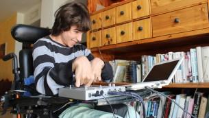 Rotem, 19 ans, est l'inspiration derrière l'invention de sa mère, le harnais Upsee. Il fait le DJ chez lui comme aux fêtes d'école (Crédit : Rebecca McKinsey/Times of Israel)