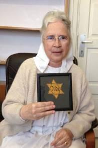 Soeur Gratia tenant un livre dont la couverture comporte une étoile jaune de David qu'un survivant de la Shoah lui a donné (Crédit :a Renee Ghert-Zand)