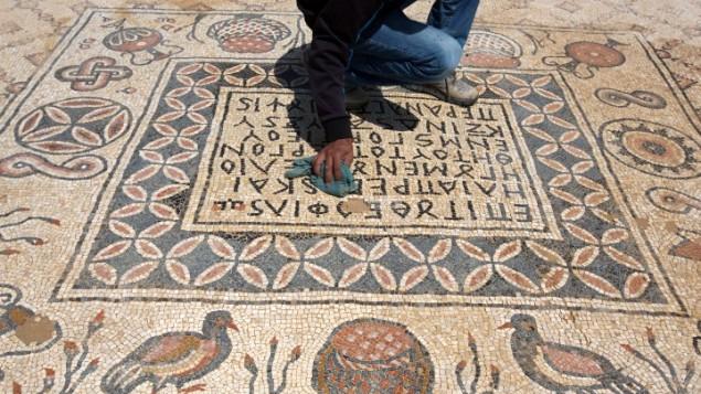 Un archéologue nettoie le sol en mosaique qui décorait le monastère du village bédouin de Hura dans la partie nord du Néguev (Crédit : Menahem Kahana/AFP)