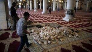 Des pierres stockées à l'intérieur de la mosquée d'Al-Aqsa, q'un employé tente de nettoyer (Crédit : Ahmad Gharabli/AFP.)