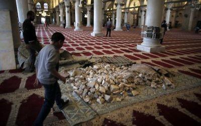 Des pierres stockées à l'intérieur de la mosquée d'Al-Aqsa, qu'un employé tente de nettoyer, en 2014. (Crédit : AFP/Ahmad Gharabli)