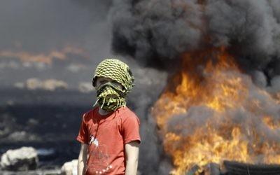 Un garçon palestinien masqué à côté de pneus en feu (Crédit : Jaafar Ashtiyeh/AFP)