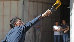 Un palestinien qui lance un cocktail molotov (Crédit : Hazem Bader/AFP)