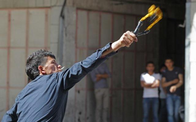 Un émeutier qui lance un cocktail Molotov (Crédit : Hazem Bader/AFP)