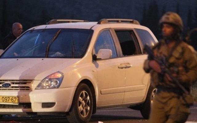 Un policier inspectant un véhicule près de la scène du crime où un policier israélien et 2 membres de sa famille ont été blessés près de Hébron (Crédit : Hazem Bader/AFP)
