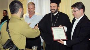 Un soldat arabe chrétien reçoit un certificat d'appréciation de la part du Père Gabriel Naddaf, à Nazareth, en 2013. (Crédit : porte-parole de l'armée israélienne)