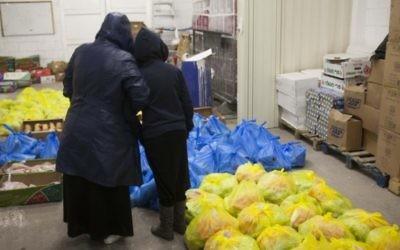 Une mère et son enfant debout devant des sacs de nourriture dans un centre pour les nécessiteux (Crédit : Yonatan Sindel/Flash 90)