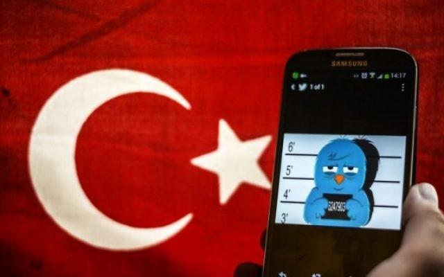 Une photo illustrant l'oiseau du logo de Twitter en état d'arrestation avec un drapeau turc en arrière-plan (Crédit : Ozan Kose/AFP)