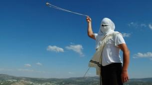 Un habitant masqué de Yitzhar, en Cisjordanie, lance des pierres à l'aide d'une catapulte, le 19 mai 2013 (Crédit : Mendy Hechtman/Flash90)