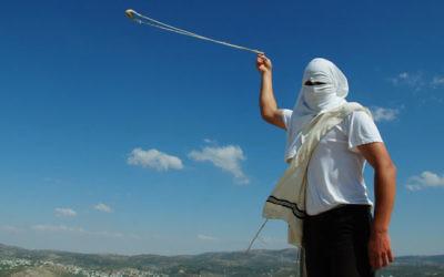 Un habitant masqué de Yitzhar, en Cisjordanie, lance des pierres avec un lance-pierre, le 19 mai 2013. (Crédit : Mendy Hechtman/Flash90)