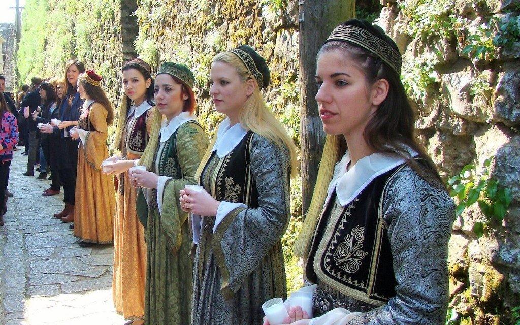 Des jeunes de la communauté juive de Ioannina, vêtu de robes traditionnelles, tiennent des bougies allumées à la mémoire des 500 enfants déportés à Auschwitz (Crédit : Gavin Rabinowitz/JTA)