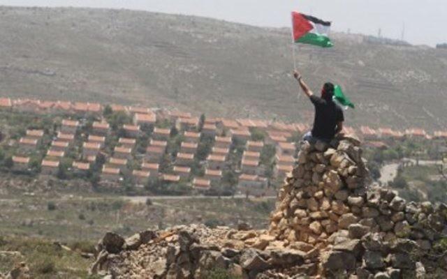 Un homme agite un drapeau palestinien devant l'implantation d'Ofra en Cisjordanie, près de Ramallah. Illustration. (Crédit : Issam Rimawi/Flash90)
